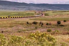 Paisaje hermoso, tren ferroviario a través del campo verde, altas montañas imagenes de archivo