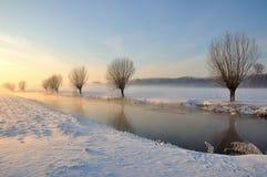 Paisaje holandés del invierno con nieve y el sol inferior Foto de archivo