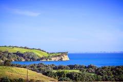 Paisaje icónico de Nueva Zelanda - colinas verdes y acantilado enormes sobre el mar azul foto de archivo libre de regalías