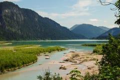 Paisaje idílico de la montaña con un río y las montañas en el fondo foto de archivo