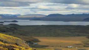 Paisaje idílico del campo con el lago, las montañas, el pueblo minúsculo y el campo de lava en otoño almacen de metraje de vídeo