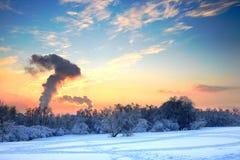 Paisaje idílico del invierno estropeado por el humo de la fábrica Imágenes de archivo libres de regalías