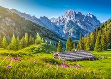 Paisaje idílico en las montañas con el chalet tradicional de la montaña en la puesta del sol imagenes de archivo