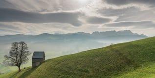 Paisaje idílico y pacífico de la montaña con un granero de madera aislado y un árbol solitario en una ladera herbosa y una gran v imagenes de archivo