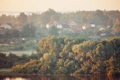 Paisaje ilustrado del otoño con el pequeño pueblo en el bosque cerca del río Fotos de archivo libres de regalías