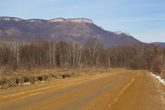 Paisaje ilustrado hermoso de estirar en la distancia del camino de la montaña con los esquemas de los árboles de montañas potente imagenes de archivo