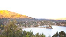 Paisaje inclinable del cambio de un pequeño pueblo al lado de un lago en las montañas fotografía de archivo libre de regalías