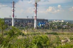 Paisaje industrial - chimeneas que fuman de una central térmico contra un cielo azul imágenes de archivo libres de regalías