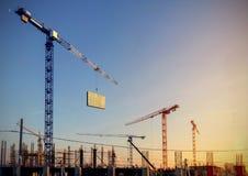 Paisaje industrial con las siluetas de grúas en los vagos de la puesta del sol Imagen de archivo libre de regalías