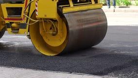 Paisaje industrial con los rodillos que rueda un nuevo asfalto en el camino reparaci?n metrajes