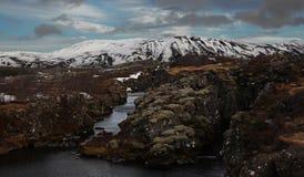 Paisaje islandés típico: El parque nacional de Thingvellir, ríos, campos de lava cubrió con nieve contra el contexto de montañas fotos de archivo