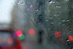 Paisaje lluvioso de la ciudad a través del parabrisas mojado Foto de archivo