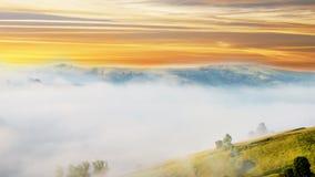 Paisaje mágico en la salida del sol en las montañas en la niebla Imagen de archivo
