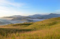 Paisaje mágico en la salida del sol en las montañas en la niebla Fotos de archivo