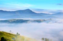 Paisaje mágico en la salida del sol en las montañas en la niebla Backgrou Foto de archivo