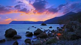 Paisaje maravilloso con las piedras en la costa en la puesta del sol Fotos de archivo libres de regalías