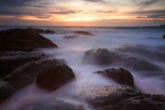 Paisaje marino con agua del movimiento que golpea rocas Foto de archivo libre de regalías