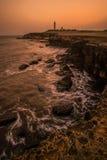 Paisaje marino con el faro en la puesta del sol Foto de archivo