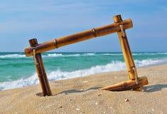 Paisaje marino con el marco de bambú en la arena de la playa Foto de archivo libre de regalías