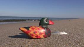Paisaje marino con el pato de madera decorativo en arena almacen de video