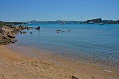 Paisaje marino con la playa arenosa, mar azul y cielo y algunos barcos amarrados foto de archivo