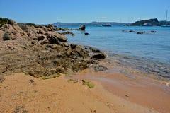 Paisaje marino con la playa arenosa, mar azul y cielo y algunos barcos amarrados fotos de archivo