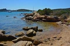 Paisaje marino con la playa arenosa, mar azul y cielo y algunos barcos amarrados foto de archivo libre de regalías