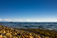 Paisaje marino con la playa de piedra cerca del lago con las montañas en el fondo Imágenes de archivo libres de regalías