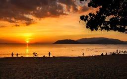 Paisaje marino con las nubes coloridas, el cielo anaranjado y The Sun en la salida del sol en Nha Trang