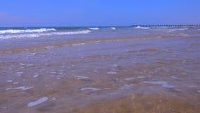 Paisaje marino con las ondas largas y el embarcadero en playa de la arena en el día soleado almacen de metraje de vídeo
