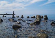 Paisaje marino con las piedras Mar y ondas azules Terraplén y faro Fotografía de archivo