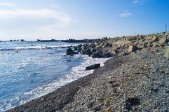 Paisaje marino con las piedras Mar y ondas azules Terraplén y faro Imágenes de archivo libres de regalías