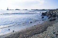 Paisaje marino con las piedras Mar y ondas azules Terraplén y faro Fotos de archivo