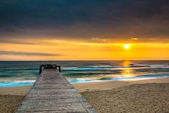Paisaje marino de la naturaleza con un embarcadero en Sandy Beach y The Sun en la salida del sol imágenes de archivo libres de regalías