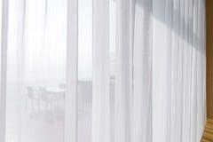 paisaje marino de la visión que mira las cortinas de la tela del blanco translúcido del paso y Foto de archivo