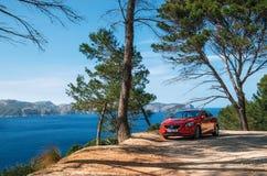 Paisaje marino del mar Mediterráneo con el coche rojo Volvo, Mallorca, España Foto de archivo libre de regalías