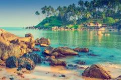 Paisaje marino escénico Cantos rodados grandes y palmeras altas en la orilla Fotos de archivo