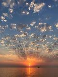 Paisaje marino escénico hermoso de la puesta del sol con la radiación de rayos del sol, de las nubes y de la agua de mar tranquil imagenes de archivo