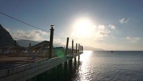 Paisaje marino hermoso, pontón con los ociosos vacíos del sol en la salida del sol en la cámara lenta metrajes