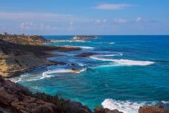 Paisaje marino maravilloso - las ondas azules salpican cerca de la orilla rocosa Fotos de archivo