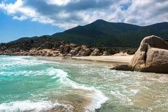 Paisaje marino tropical con una playa, un agua de la turquesa, rocas, montañas y nubes salvajes en el cielo azul foto de archivo