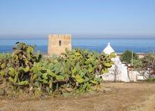 Paisaje mediterráneo en Puglia con el mar, los higos chumbos, trullo y la torre vieja fotografía de archivo