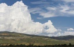 Paisaje, montañas y nube enorme en el cielo azul Imagen de archivo