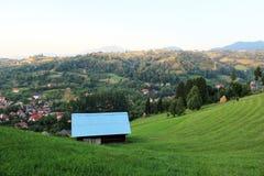 Paisaje montañoso del verano con una choza en la vanguardia foto de archivo