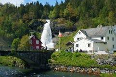 Paisaje noruego con las casas y la cascada fotos de archivo