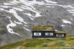 Paisaje noruego tradicional de la montaña con la casa de madera negra Imagen de archivo