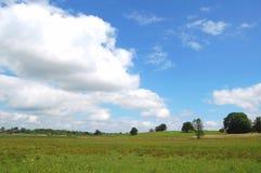 Paisaje nublado con el cielo azul imagenes de archivo
