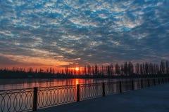 Paisaje nublado de la puesta del sol sobre la opinión congelada del río en el invierno foto de archivo