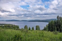 Paisaje nublado del sammer del lago con una colina floreciente y las montañas en la distancia Fotografía de archivo libre de regalías