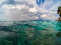 Paisaje oceánico con agua transparente y el cielo azul Mirada azul de la agua de mar a través Fotos de archivo